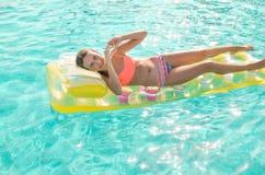 Lächelndes jugendlich Mädchen, das in das Türkispool im hellen korallenroten Bikini auf einer gelben Matratze schwimmt Mädchen ze stockbild