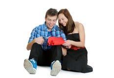 Lächelndes Jugendliche- und Jungenausschnitt-Valentinsgrußinneres aus rotem Papier mit Scheren heraus Lizenzfreie Stockbilder