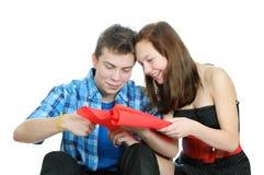 Lächelndes Jugendliche- und Jungenausschnitt-Valentinsgrußinneres aus rotem Papier mit Scheren heraus Lizenzfreie Stockfotos