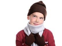 Lächelndes jugendliches Kind zusammengerollt in der Winter-Kleidung Stockfoto