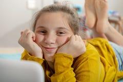 Lächelndes Jugendlichmädchen, das auf dem Bett, unter Verwendung des Laptops liegt stockbild