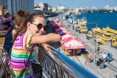 Lächelndes Jugendstudentenmädchen, das auf dem Damm nahe steht Lizenzfreie Stockfotos