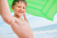 Lächelndes Jungenseeporträt mit grüner Luftschwimmenmatratze Lizenzfreies Stockfoto