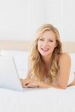 Lächelndes junges blondes Lügen auf ihrem Bett unter Verwendung des Laptops Stockbilder