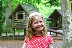 Lächelndes junges blondes Mädchen, das aus- nasses, unordentlich, schmutzig, durchnässt und glücklich spielt Stockfoto
