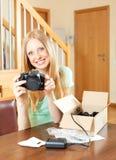 Lächelndes junges blondes am Tisch mit neuer Digitalkamera Stockfoto