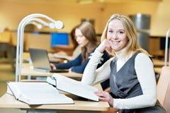 Lächelndes junges Buch der erwachsenen Frau Lesein der Bibliothek Lizenzfreie Stockbilder