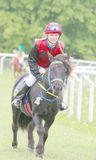 Lächelndes junges Mädchen, das auf einem schwarzen Pony sitzt Lizenzfreies Stockfoto