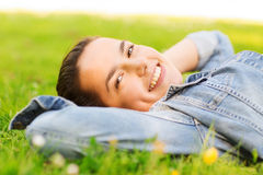 Lächelndes junges Mädchen, das auf Gras liegt Lizenzfreie Stockbilder