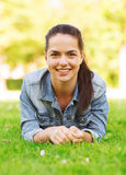 Lächelndes junges Mädchen, das auf Gras liegt Stockfotos