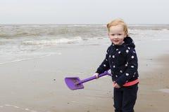 Lächelndes junges Mädchen, das an der Nordsee-Küste spielt Lizenzfreie Stockfotos