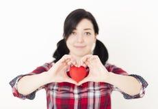 Lächelndes junges Mädchen, das ein kleines rotes Herz und ihre Finger in Form von Herzen hält stockfoto