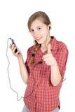 Lächelndes junges Mädchen, das Musik auf ihrem Mobiltelefon hört und den Daumen oben lokalisiert auf Weiß zeigt Stockfotografie