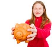 Lächelndes junges Mädchen, das Sparschwein hält Stockbilder