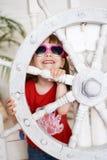 Lächelndes junges Mädchen in der Sonnenbrille mit Lenkrad Stockfoto