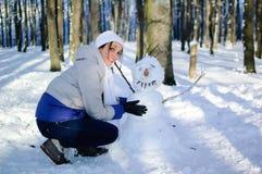 Lächelndes junges Mädchen im weißen Hut und im Schal, die lustigen Schneemann im Park während eines sonnigen Tages umarmt Blauer  stockfotografie