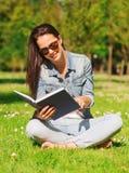 Lächelndes junges Mädchen mit dem Buch, das im Park sitzt Stockbilder