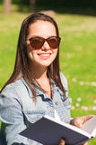 Lächelndes junges Mädchen mit dem Buch, das im Park sitzt Lizenzfreie Stockfotografie