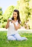 Lächelndes junges Mädchen mit dem Smartphone, der im Park sitzt Stockbild