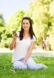 Lächelndes junges Mädchen mit dem Smartphone, der im Park sitzt Stockfotografie