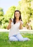 Lächelndes junges Mädchen mit dem Smartphone, der im Park sitzt Lizenzfreie Stockfotografie