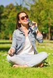 Lächelndes junges Mädchen mit Flasche Wasser im Park Stockfoto