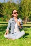 Lächelndes junges Mädchen mit Tasse Kaffee im Park Stockfoto