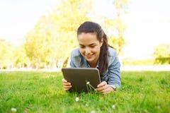 Lächelndes junges Mädchen tablet den PC, der auf Gras liegt Lizenzfreie Stockbilder