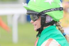 Lächelndes junges Mädchen, welches die grüne Kleidung sitzt auf einem Pony trägt Stockbilder