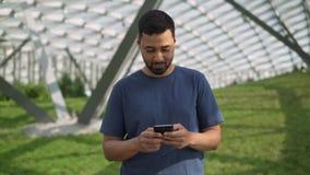 Lächelndes junges Mannsimsen und surfende Stellung des Netzes auf grünem Rasen stock video