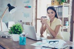 Lächelndes junges Mulattemädchen trinkt Kaffee am Bruch herein von lizenzfreies stockfoto
