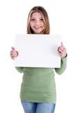 Lächelndes junges schönes Mädchen, das weißen Vorstand anhält Lizenzfreie Stockfotografie