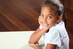 Lächelndes junges Schulemädchen 10, das im Klassenzimmer sitzt Stockbild