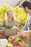 Lächelndes kaufendes Gemüse des blonden Kunden Stockfotos