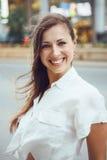 Lächelndes kaukasisches Frauenmädchen mit blauen Augen mit dem unordentlichen blonden langen Haar am windigen Tag im Freien, geto Stockbild