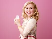 Lächelndes Kind auf rosa Hintergrund mit organischem Jogurt des Bauernhofes Lizenzfreie Stockfotos