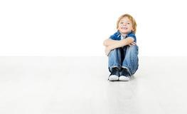 Lächelndes Kind, das auf weißem Boden sitzt Stockfoto