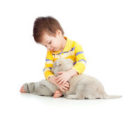 Lächelndes Kind, das einen Welpen umarmt lizenzfreie stockfotografie