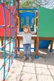 Lächelndes Kind, das im Spielplatz hängt Stockbild
