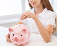 Lächelndes Kind, das Münze in großes Sparschwein setzt Stockbilder