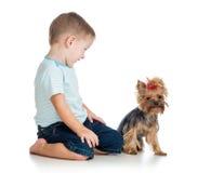 Lächelndes Kind, das mit einem Hündchen spielt Stockbild