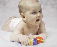 Lächelndes Kind, das mit Spielwaren spielt Lizenzfreies Stockfoto