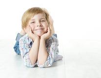 Lächelndes Kind, das sich, Kamera betrachtend hinlegt Lizenzfreie Stockfotos