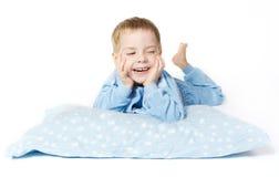 Lächelndes Kind, das sich mit Kissen hinlegt Stockfotos