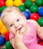 Lächelndes Kind, das unter bunten Kugeln spielt Stockfotos