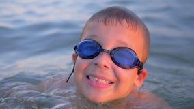 Lächelndes Kind in den Schutzbrillen schwimmend im Meer stock footage