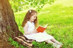 Lächelndes Kind des kleinen Mädchens, das ein Buch auf dem Gras nahe Baum liest Stockfoto