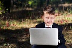 Lächelndes Kind im Anzug, der die Kamera mit einem Laptop betrachtet Stockbilder