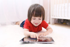 Lächelndes Kind im roten T-Shirt mit Tablet-Computer Lizenzfreie Stockfotografie