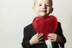 Lächelndes Kind mit rotem Herzen. Vier Jahre alte Jungen-mit Herz-Symbol. Reizendes Kind im schwarzen Anzugs-Valentinstag stockfotografie